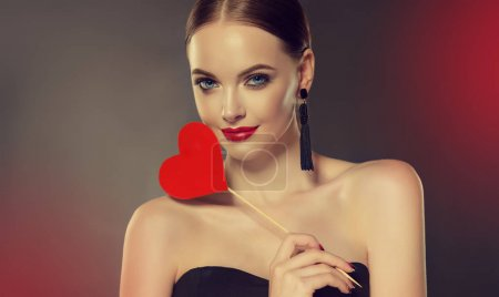 Beautiful girl with earrings and red heart. Beauty and accessories.