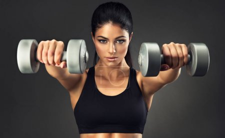 Beautiful fitness woman with lifting dumbbells . Sporty girl showing her well trained body . Well-developed muscles by strength training .