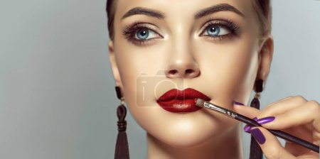 Makeup artist applies red lipstick . Beautiful woman face. Hand of make-up master, painting lips of young beauty model girl . Make up in process
