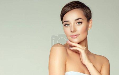 Foto de Hermosa mujer joven con la piel limpia y fresca. Cuidado de la cara. Tratamiento facial. Cosmetología, belleza y spa. Chica con pelo corto - Imagen libre de derechos
