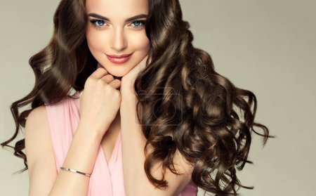 Photo for Brunette girl with long , healthy and shiny curly hair . Beautiful model woman with wavy hairstyle .Care and beauty - Royalty Free Image