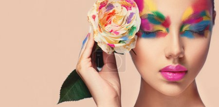 Photo for Beautiful girl model with multi-colored paints on her face. Woman with rose flower and bright color make-up. Cosmetics, beauty and makeup. Spring and summer flowering shopping - Royalty Free Image