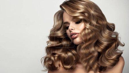 Photo pour Beauté fille brune aux cheveux longs et brillants ondulés. Belle femme modèle avec coiffure bouclée. Perm, trichologie et soins - image libre de droit