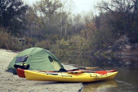 Camping with kayaks on the river bank.