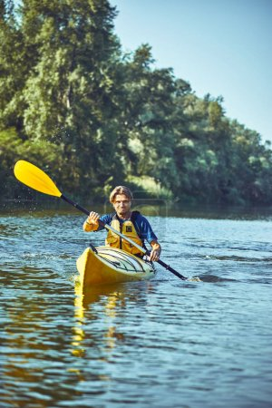 A canoe trip along the river along the forest in summer.