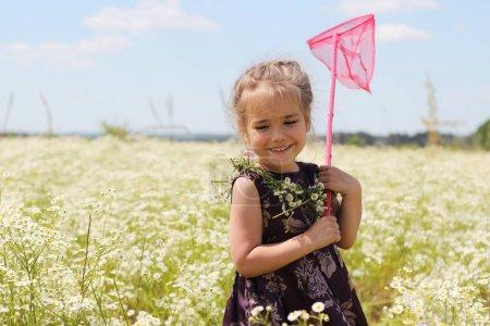 Photo pour Mignonne petite fille drôle avec guirlande de fleurs sauvages sur son cou et papillon net restant dans le champ de la camomille, beauté et soins de santé, enfance heureuse, vacances actives, close-up portrait en plein air - image libre de droit