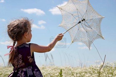 Photo pour Mignonne petite fille qui s'étend de parasol soleil ajouré dans le bleu du ciel alors qu'elle marche entre le champ de la camomille en été, charme chic minable, notion de pays style, beauté et mode, ete outdoor - image libre de droit