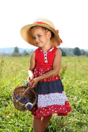 Photo pour Jolie petite fille au chapeau de paille et avec panier de paille marchant sur l'alpage et la cueillette des fleurs et des baies, humeur d'été, vacances, voyage concept, portrait lifestyle en plein air - image libre de droit