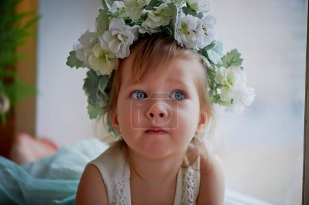 Beautiful little girl in a wreath on the head in green and white. Party dress,  Princess.