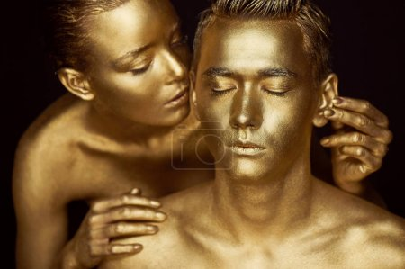 A girl and a guy covered in gold paint. With my eyes closed. The girl leaned in and kisses his ear