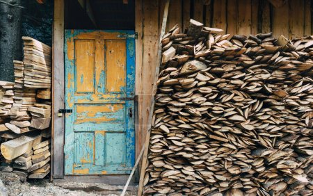 Photo pour View at a village storage house for tools and fire woods. Vintage painted door in blue color. Paint is partially pilled off. Fire woods stored under a roof near a storage village house. - image libre de droit