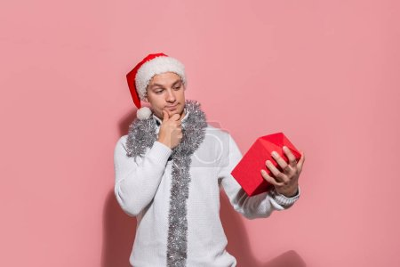 Photo for Man in a white sweater and red Santa hat looking at the red box to find out what gifts are in. Merry Christmas and happy New Year - Royalty Free Image