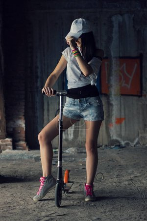 Young athlete woman is standing near her kick scooter inside of
