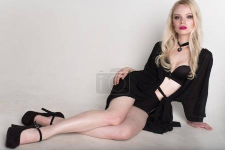 young sexy smiling blonde woman in black lingerie posing on white background.