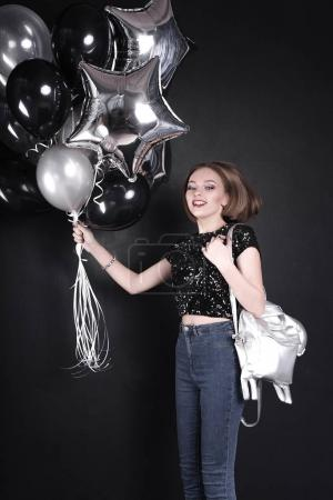 Close up fashion portrait of a young beautiful elegant girl with bright party make up in evening black sequin top. She is keeping silver stars balloons in her hand. Girl at the party. Retouched shot