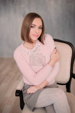 Soft photo of fresh young woman in pink tender sweater smiling. Pretty girl enjoying early sunny morning at home.