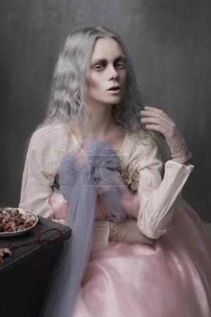 Photo pour Sombre portrait halloween de vilaine fille zombie effrayant assis dans une chaise et recueillir des cœurs. Photo conceptuelle - image libre de droit