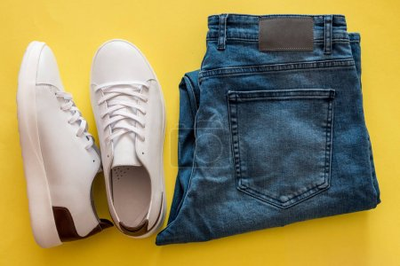 Set of white sneakers and blue jeans on yellow background.