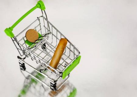 Photo pour Un chariot de supermarché avec une miche de pain et une pièce de monnaie - image libre de droit