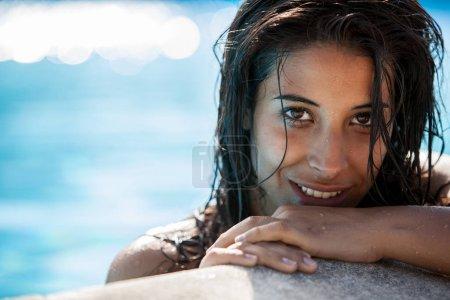 beautiful young latina woman in pink bikini portrait at swimming pool