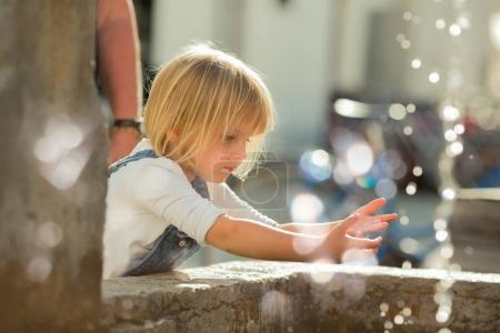 young baby caucasian blonde girl washing hands at city fountain