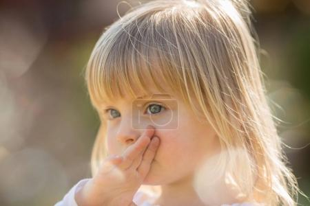 Photo for Candid serious thinking or sad young baby caucasian blonde girl portrait outdoor. - Royalty Free Image