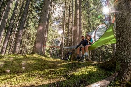 couple relaxing in hanging tent camping in forest