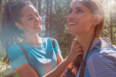woman helping friend at hiking trail