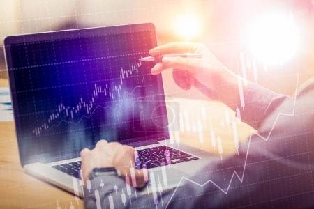 Businessman working on global financial trading growth analysis strategy using laptop.Modern business innovation investment concept.Office project with virtual forex graph and chart data interface