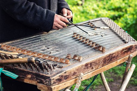 Cimbalom very special string wooden musical instrument. A street musician plays a cimbalom. The cimbalom, tambal, hammered dulcimer with player hands, hammers. Ukrainian national instrument folk music