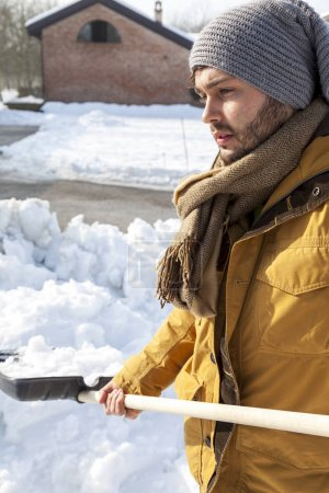 young man shoveling snow near a farm