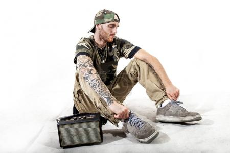Photo for Sitting tattooed rap singer posing in studio with an amplified radio on a white background - Royalty Free Image