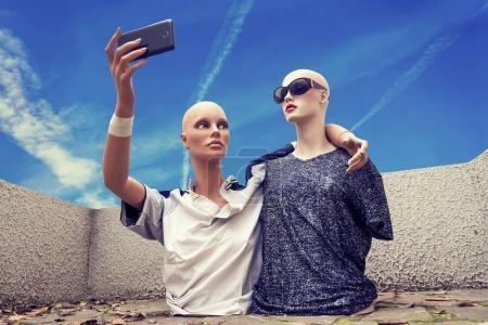 Photo pour Paire de mannequins prendre un selfie habillé dans les années soixante-dix vêtements de sport devant un ciel bleu - image libre de droit