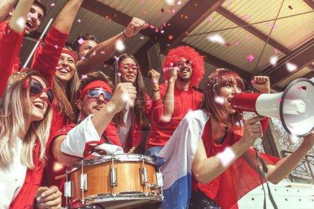 Foto de Grupo de aficionados vestidos de rojo, viendo un evento deportivo en las gradas de un estadio - Imagen libre de derechos