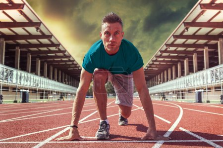 Photo for Young athlete determined to start blocks ready for the fast race in outdoor stadium - Royalty Free Image