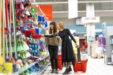 Photo for Couple of young pretty multi-ethnic women are shopping in the cleaning department at the supermarket - Royalty Free Image