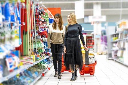 Photo pour Quelques jeunes jolies femmes multi-ethniques font du shopping dans le département de nettoyage au supermarché - image libre de droit