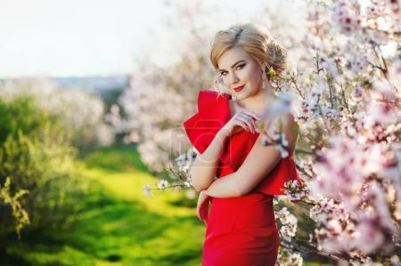 beautiful young woman in a red dress near the blossoming spring tree
