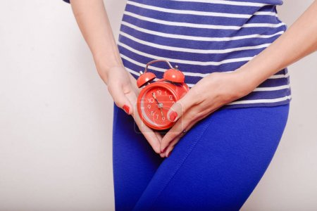 Female holding red alarm clock feeling stomach pain or hunger.