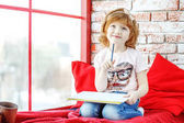 Beautiful kid fantasizes and paints on the windowsill. The conce