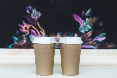 Photo pour Tasses de café à emporter sur le bar avec motif de fleurs - image libre de droit