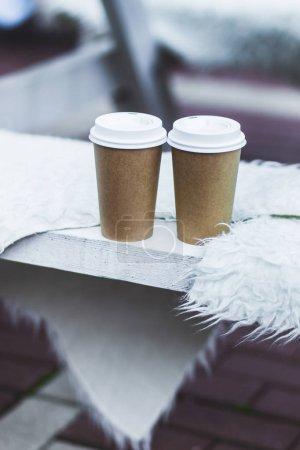 Photo pour Tasses de café à emporter sur banquette recouverte de laine naturelle pour plus de chaleur en hiver - image libre de droit
