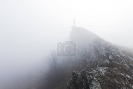 Photo for Man standing alone in the fog in mountains - Royalty Free Image