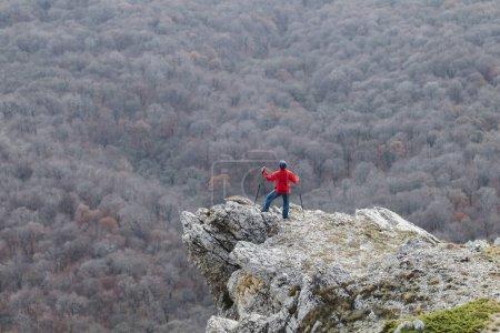 Man climbing to the edge of rock