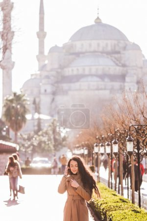 Woman in beige coat walks in the area near the Blue Mosque at beautiful sunny weather