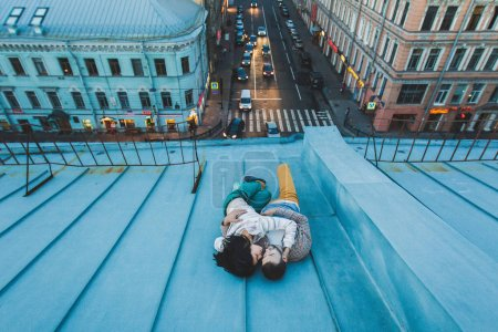 Young hipster couple lying on the roof