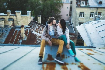 Young happy couple sitting on the roof