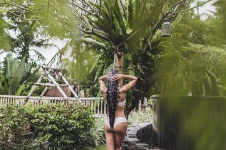 Woman taking shower in tropical garden