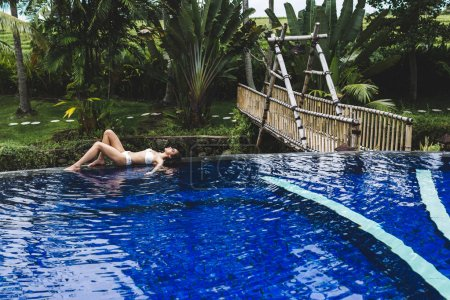 Woman relaxing in pool in tropical Bali