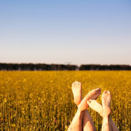 Bare feet of couple in field